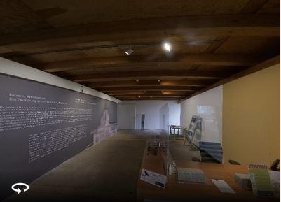 """Blick auf den Eingang zur Ausstellung """"Die Zerstörung des jesidischen Kulturerbes"""" von Forensic Architecture mit Rezeption des Künstlerhauses"""