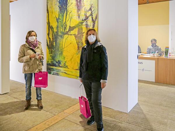 In einem Ausstellungsraum, an dessen Wänden großformatige Kunstwerke hängen, stehen zwei Besucherinnen mit FFP2-Gesichtsmasken. Im Hintergrund ist der Empfang zu sehen, an dem ein Mitarbeiter des Künstlerhauses hinter einer Plexiglasscheibe und ebenfalls mit FFP2-Maske zu sehen ist.