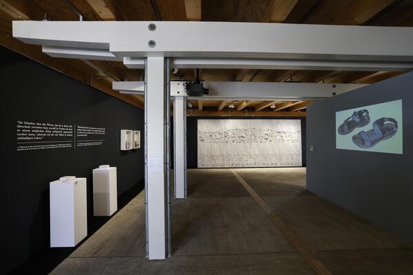 Blick in die Ausstellung mit Bildern und Text an den Wänden, einem großen Kunstwerk an der Wand, mehreren Stelen mit Kunstwerken